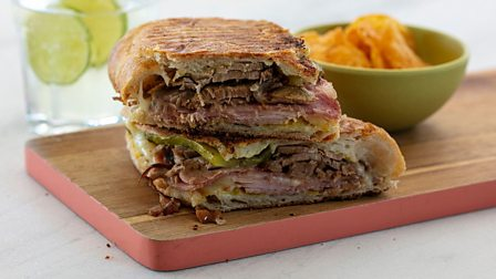A cubano sandwich with bowl of crisps next to it.