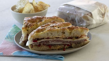Muffaletta sandwich with Italian cured meats and cheeses on focaccia