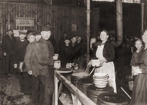 Men and boys waiting in line at a postwar German soup kitchen in a market hall in Berlin