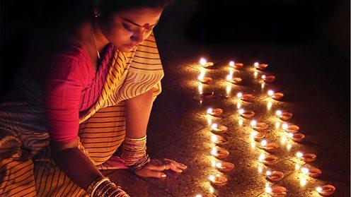 Woman lighting earthen lamps during Diwali