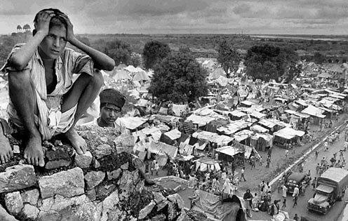 A distraught boy sat near a refugee camp in Delhi during the Partition of India.