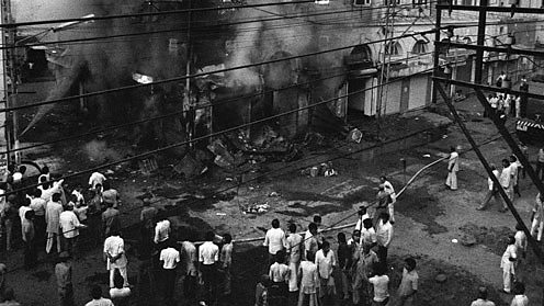 Indian bystanders look on as a building belonging to Sikh merchants burns in Delhi.