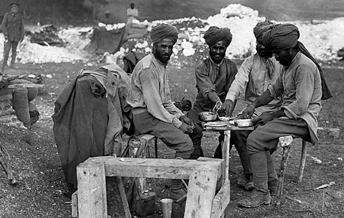 Indian soldiers wearing traditional turbans relax around a makeshift dinner table