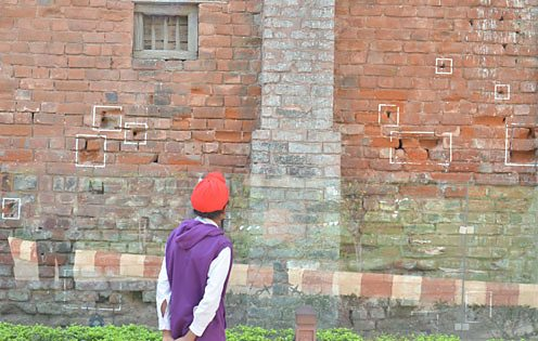 A boy looks at a bullet-ridden wall at the site of the Amritsar massacre.