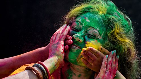 Indian woman covered in coloured powder during a Holi festival in Kolkata, India