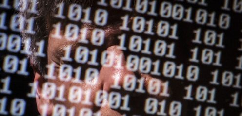 Man's face reflected on computer screen showing binary numbers