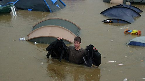 Man wades through floodwater at Glastonbury festival camp site