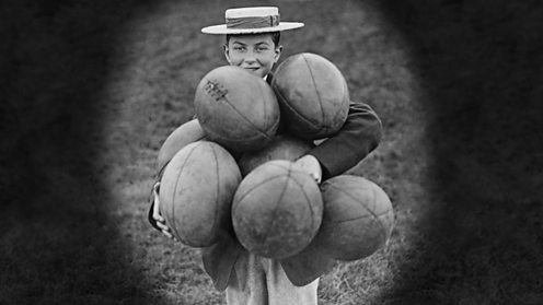 Harrow boy with armful of rugby balls circa 1935