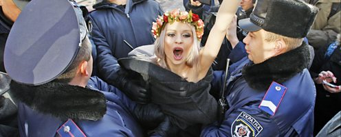 Ukrainian policemen detain a Femen activist during the group's topless protest.