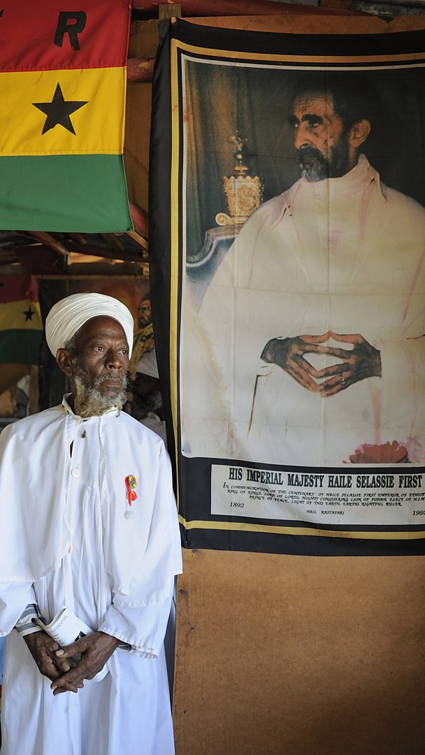 A Rastafarian stands next to a banner of Haile Selassie. Kingston, Jamaica.