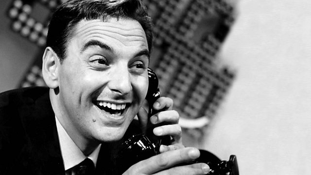 Black and white photo of young Bob Monkhouse. Bob is holding a phone and grinning inanely