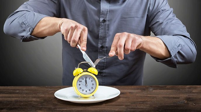 Man sat down to eat with a clock next to him