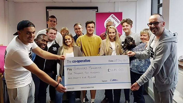 Members of Survivors Manchester holding a cheque for money they've raised