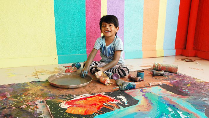 Advait Kolarkar smiling and painting a picture on the floor in a brightly-coloured room