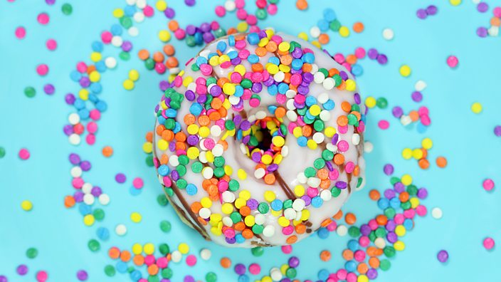 A doughnut with bright coloured sprinkles on a bright blue background