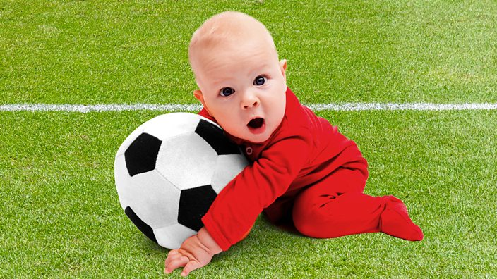 Baby with a football on a pitch