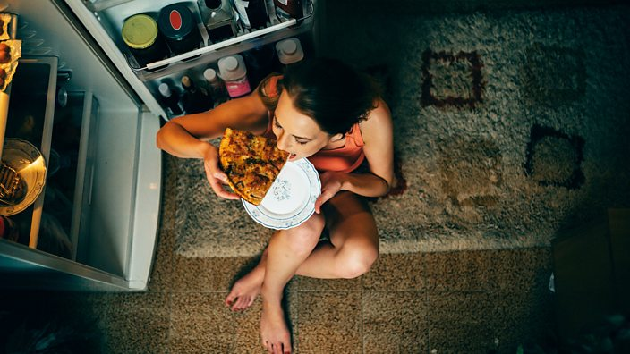 Thin woman eating pizza out of a fridge