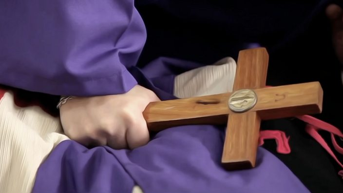 Priest holding a wooden cross