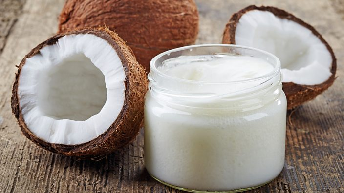 A jar of coconut oil on a table next to some coconuts