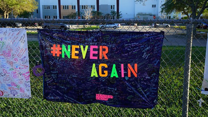 A banner with the hashtag 'never again' hung outside Marjory Stoneman Douglas High School