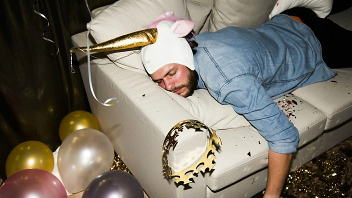 A man in a unicorn party hat slumped on a sofa asleep