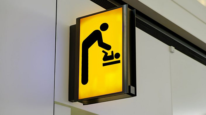 Yellow toilet sign showing male changing baby