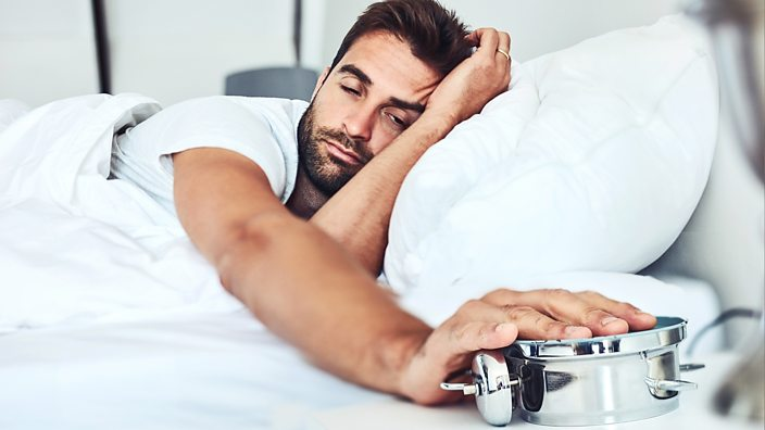 A photo of a man turning over his alarm clock so he can stay in bed