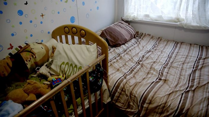 Photo of the interior, showing her bed and a baby's cot pushed right up against one another