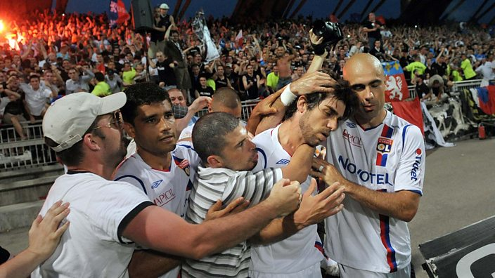 Juninho is mobbed by Lyon fans and team-mates