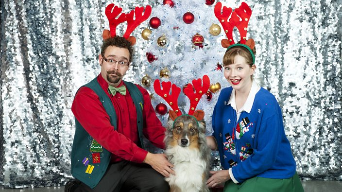 A man, a woman and a dog in Christmas outifts
