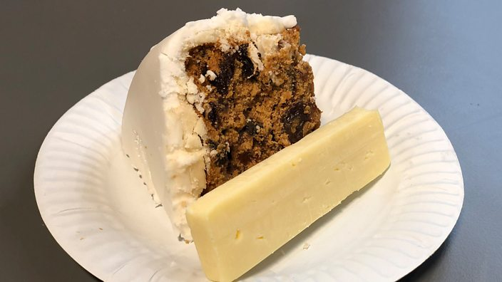 A photo of a slice of Christmas cake and a slice of cheese on a paper plate
