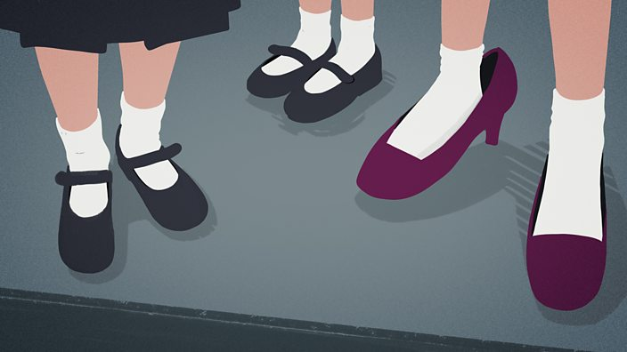 Three childrens feet outside the school gate, the elder one is wearing her mum's shoes and they're too big