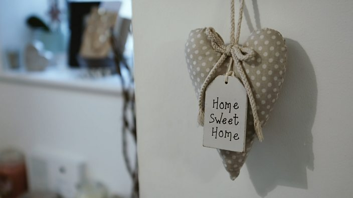 A trinket with the word 'home sweet home' hangs from a door in Alex's family home