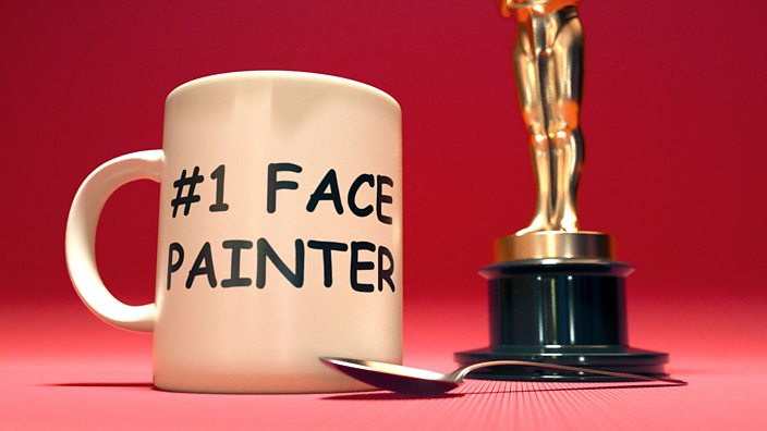A mug with the words #1 face painter on the side stood next to an oscars award trophy