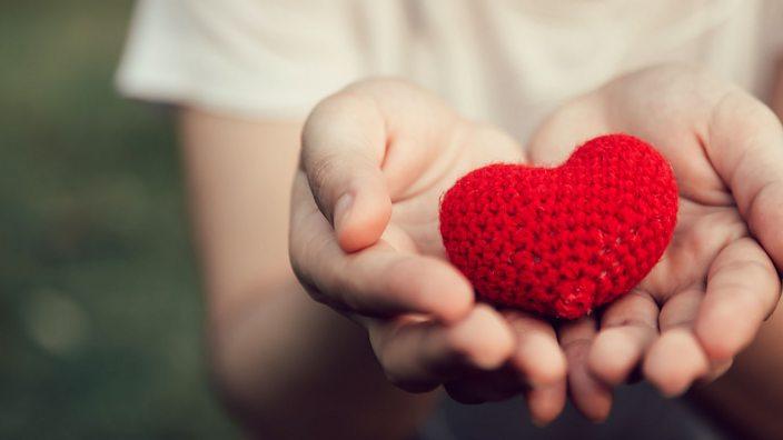 A hand holding a crocheted heart