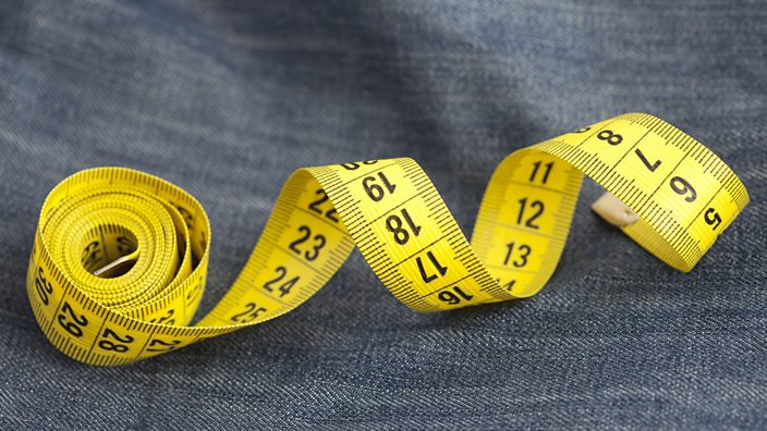 A measuring tape on a pair of jeans