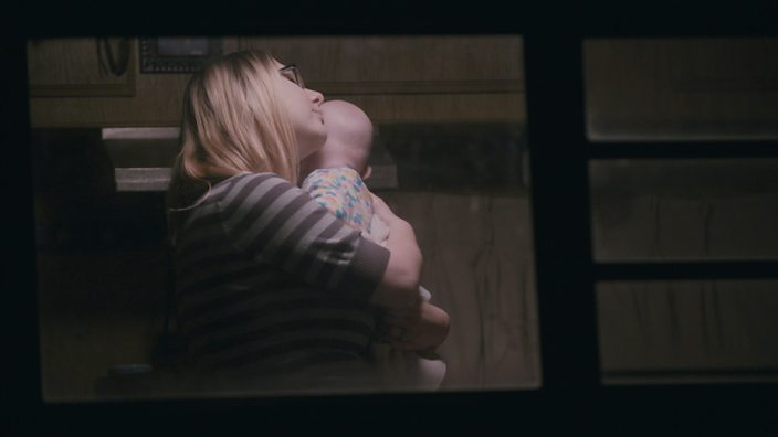 A shot through her trailer window showing Heather holding her baby