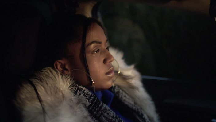 A photo of Chanell looking pensively out a car window