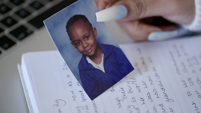 A shot of Chanell holding a primary school photo of her brother Daniel