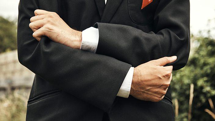 Waleed clutching blazer
