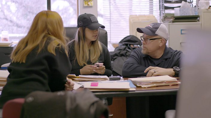 Stacey Dooley sits at a desk in the bounty hunters office with married couple Scott and Lydia