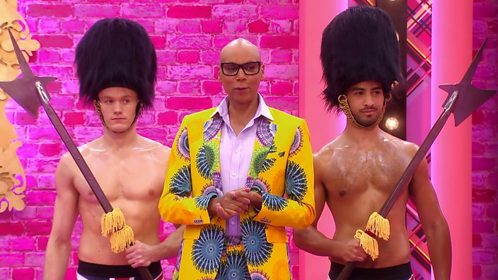 Drag Race UK host RuPaul stands against a pink wall wearing a patterned yellow blazer with two bare-chested royal guards stood either side of him