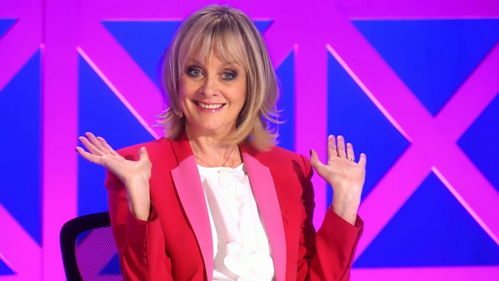 Dame Twiggy sits wearing a pink blazer on the judges panel of RuPaul's Drag Race UK