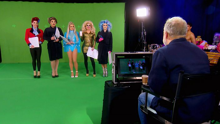 The queens line up in front of a green screen