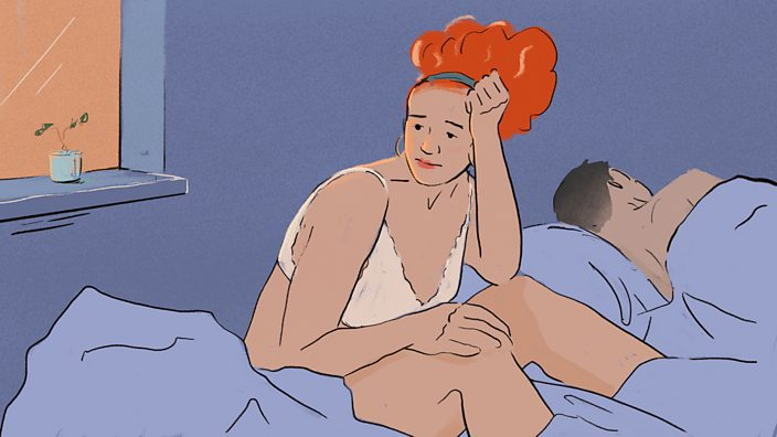 Woman in bed with a sleeping man looking regretful
