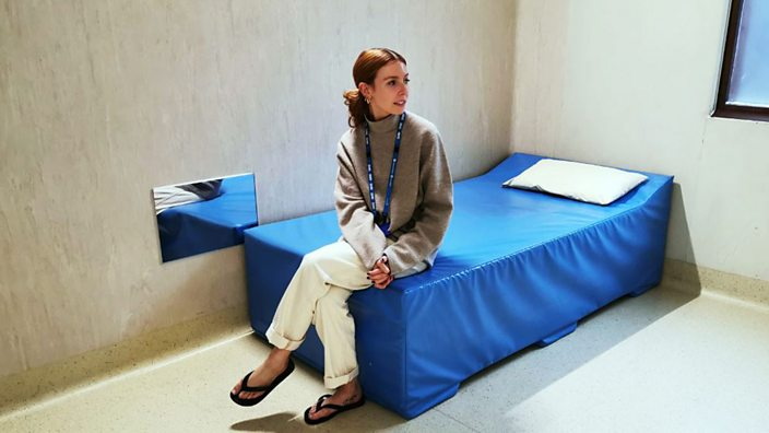 Stacey Dooley sits on a bed in a psychiatric ward