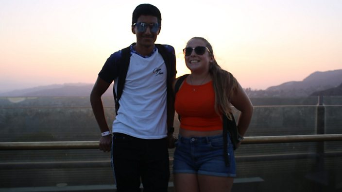 Image of Lucy and Arun posing for a photo with a beautiful mountain view behind them