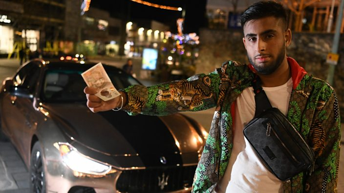 Gurvin standing in front of his Maserati holding cash in