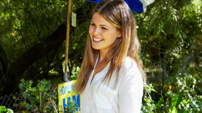 Belle at a food market, smiling, holding a wicker basket wearing a white shirt and jeans
