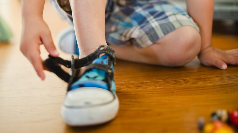 A child putting their shoe on.